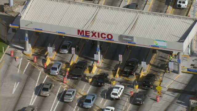 Cars move across the international border into Mexico.