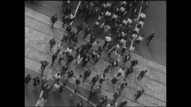 stockvideo's en b-roll-footage met cars move after pedestrians clear the crosswalk by the tokyo station. - 1963