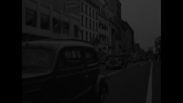 VS cars move down street under banner of pennants overhead / boys pass camera in convertible women cross street smiling people walk along side of...