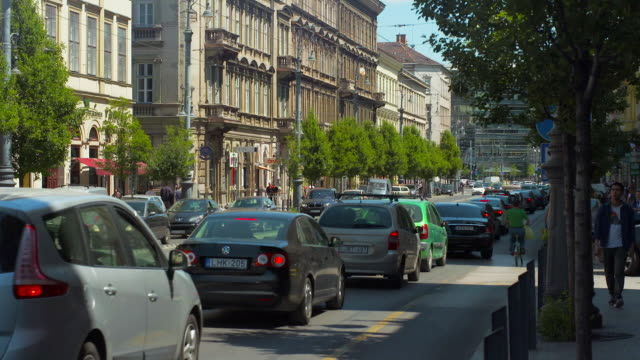 Cars Move Through Dense Traffic in Front of Elaborate Architecture in Budapest