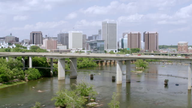 WS AERIAL POV Cars moving on bridge with modern cityscape, river and rocks seen in foreground / Richmond, Virginia, United States