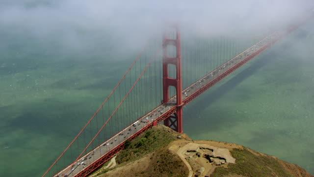 vidéos et rushes de ws aerial pov cars moving on golden gate bridge with fog, city in distance / san francisco, california, united states - inclinaison vers le bas