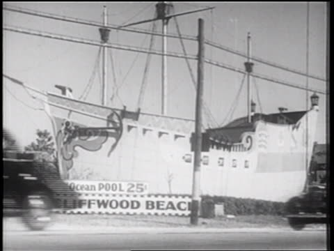 stockvideo's en b-roll-footage met b/w 1939 cars moving on highway past boat + sign for cliffwood beach / new jersey / documentary - tweebaansweg