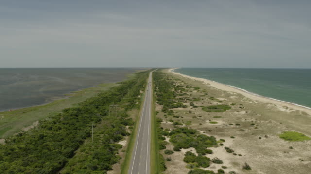 WS TD AERIAL POV Cars moving on road, beach in background / Cape Hatteras, North Carolina, United States