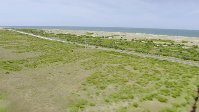 ws pan aerial pov cars moving on road, beach in background / cape hatteras, north carolina, united states - north carolina beach stock videos & royalty-free footage