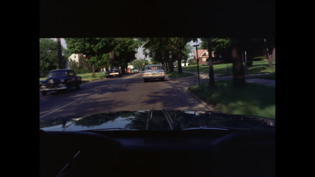 ms pov cars moving on road in suburban residential area / united states - 1960 stock-videos und b-roll-filmmaterial