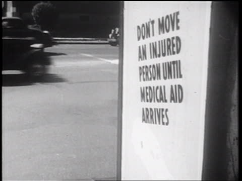 "vidéos et rushes de b/w 1939 cars moving past sign: ""don't move an injured person until medical aid arrives"" / doc. - message"