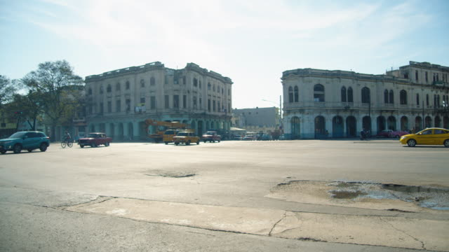 cars on a road intersection and old colonial-style buildings in downtown havana, cuba - 荒廃した点の映像素材/bロール
