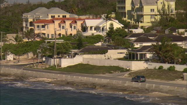 AERIAL Cars on coastal road along shoreline with trees and island homes, Nassau, Bahamas
