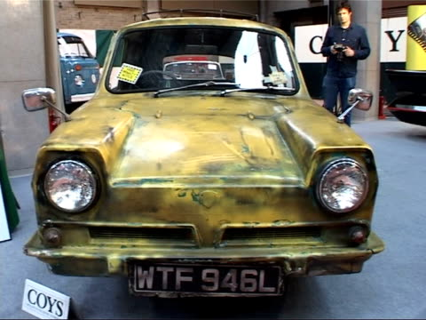 cars on display at auction house; battered yellow reliant three-wheeled van decorated with 'trotters independent trading' livery, used for bbc... - only fools and horses fernsehsendung stock-videos und b-roll-filmmaterial