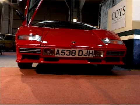 Cars on display at auction house Bright red 1984 Lamborghini Countach once owned by Barry Gibb showing lifting roof dashboard and steering wheel