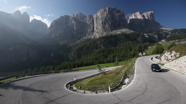 ws cars on gardena pass with sella group in background / alto adige, italy   - 曲線点の映像素材/bロール