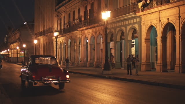 cars on illuminated street by buildings in city - cuba stock videos and b-roll footage