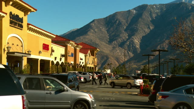 vídeos de stock e filmes b-roll de ms, cars on parking lot in front of shopping mall, mountains in background, cabazon, california, usa - shopping centre