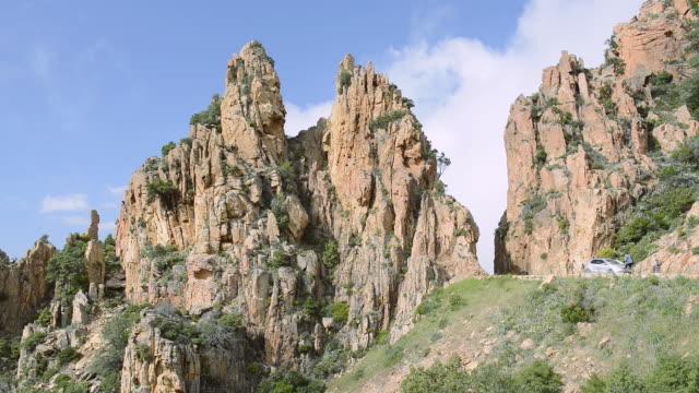 ms cars on the road through the fantastic rock landscape of the calanche of piana, unesco world heritage site / gulf of porto, corsica, france - ピアナ点の映像素材/bロール