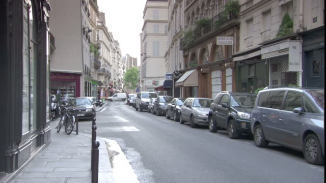 Cars park along a narrow street where a businessman walks.
