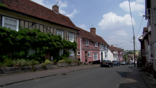 cars park along a street in a quaint village. available in hd. - village stock videos & royalty-free footage