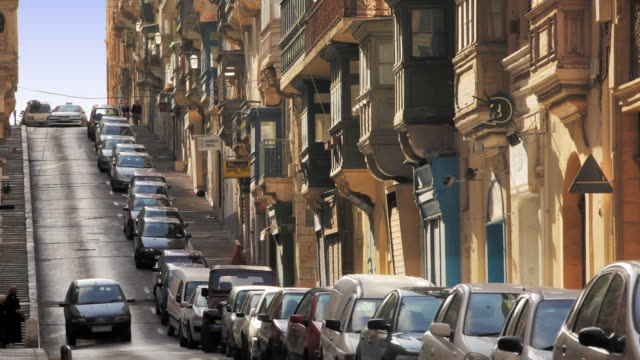 cars park end-to-end in front of row houses along a one-way street in la valetta. - valletta stock videos & royalty-free footage
