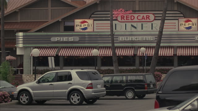 Cars park in the parking lot in front of the Red Car Diner.