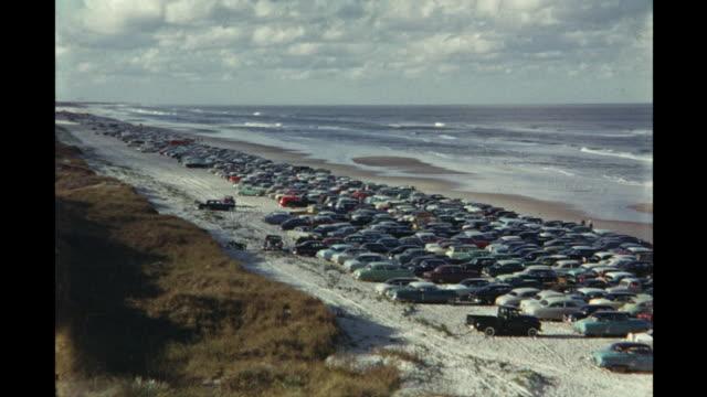 cars parked along beach and car race at daytona international speedway daytona beach florida usa - circuito di daytona video stock e b–roll