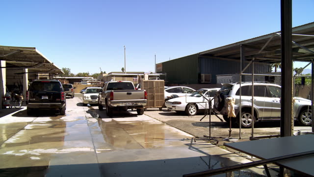 WS PAN Cars parked in main driveway of auto body shop / Cathedral City, California, USA