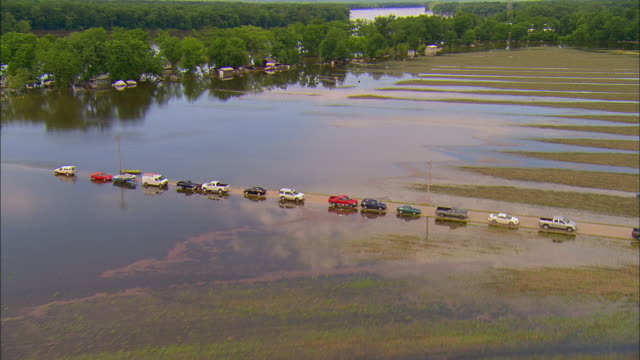 Cars parked in row on dry road surrounded by floodwaters/ Foley Missouri