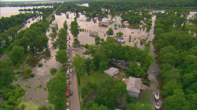 Cars parked in row on dry road surrounded by floodwaters/ Group of boats in floodwaters near house/ Foley Missouri