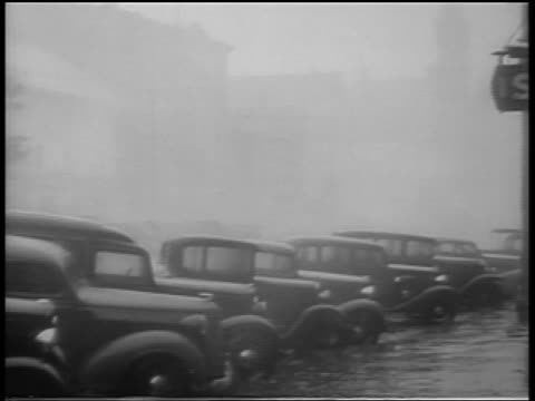 B/W 1938 cars parked on flooded street in rain during hurricane / Northeast US / newsreel