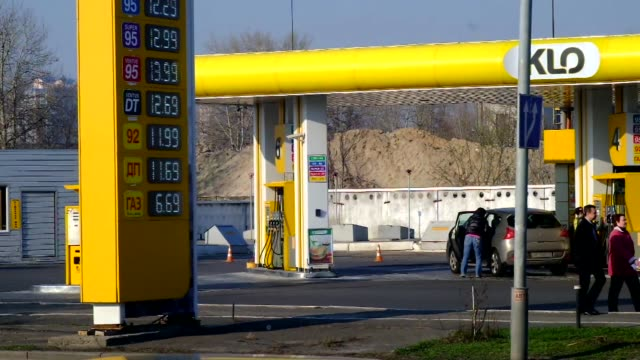 cars pass a sign advertising foreign exchange rates including rubles euros and dollars outside a currency store in kiev ukraine on sunday march 23... - gas station attendant stock videos and b-roll footage