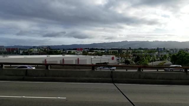 cars pass along an overpass of the 580 freeway at dawn rush hour, with the town of emeryville, california visible in the background, 2019. - emeryville stock videos & royalty-free footage