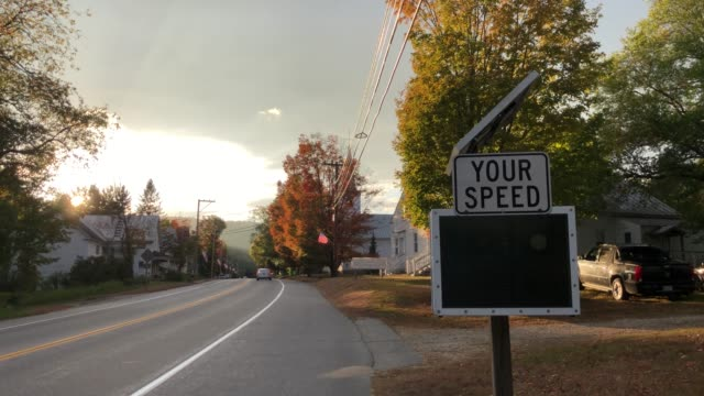 cars pass by digital speed sign on roadside in rumford, maine usa during autumn - orthographic symbol stock videos & royalty-free footage