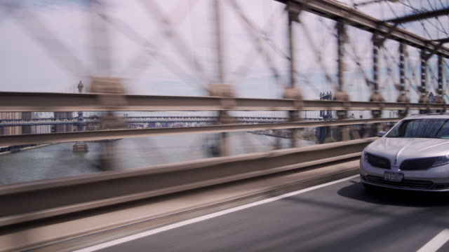 cars pass by the camera as it crosses the brooklyn bridge looking toward the manhattan bridge over the east river. - ブルックリン橋点の映像素材/bロール