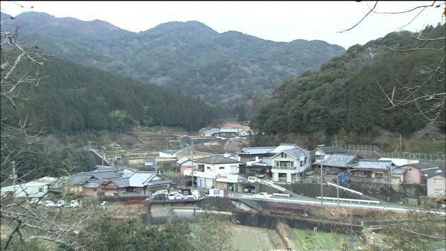 Cars pass through a Japanese mountain village.