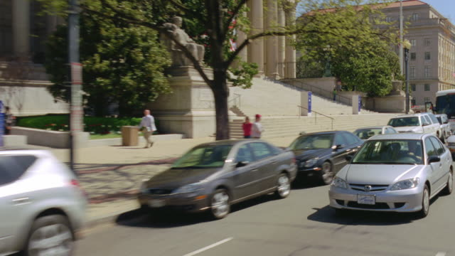 vidéos et rushes de ms pov cars passing along with washington dc streets (pennsylvania and constitution ave), tower of old post office and newseum national art gallery are visible briefly - style néoclassique