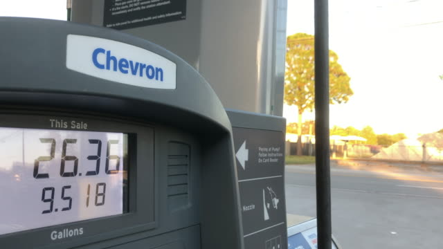cars passing by a chevron gas station in houston texas - currency symbol stock videos & royalty-free footage