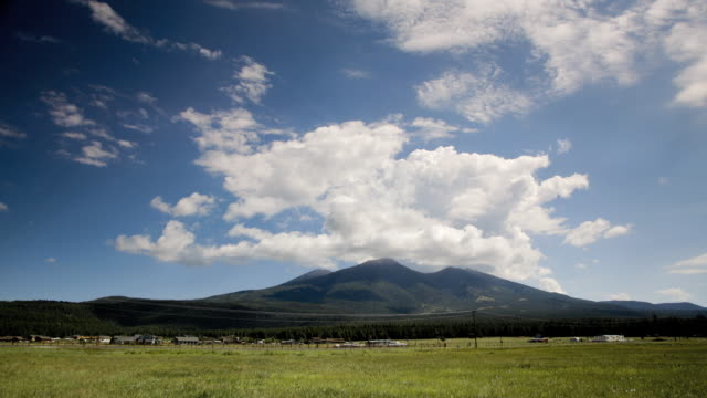 ws t/l cars passing by highway with san francisco peaks in background / flagstaff, arizona, usa - flagstaff arizona video stock e b–roll