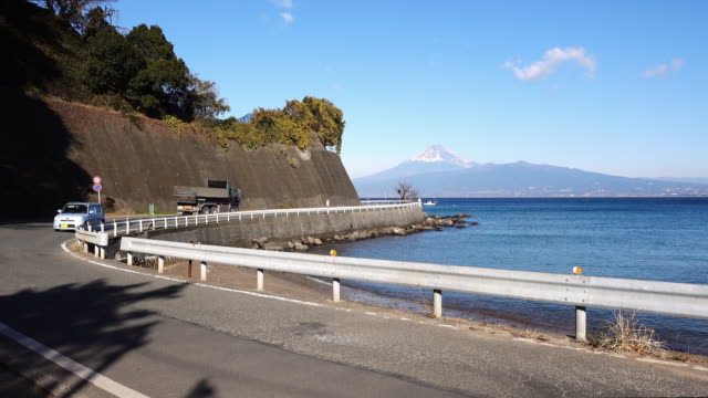 cars passing by the seaside road with mt. fuji in the background - トラック点の映像素材/bロール