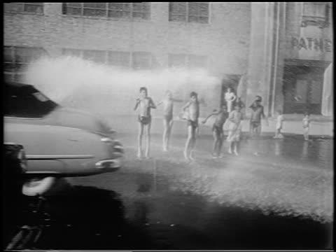 stockvideo's en b-roll-footage met cars passing children jumping around in fire hydrant spray on city street / newsreel - alleen jongens