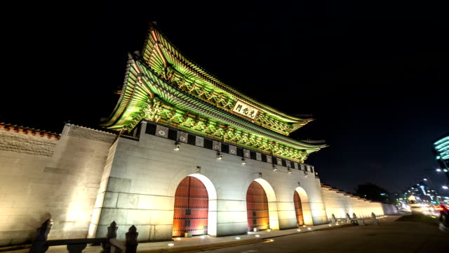 Cars passing in front of Gwanghwamun Gate of Gyeongbokgung Palace and modern buildings