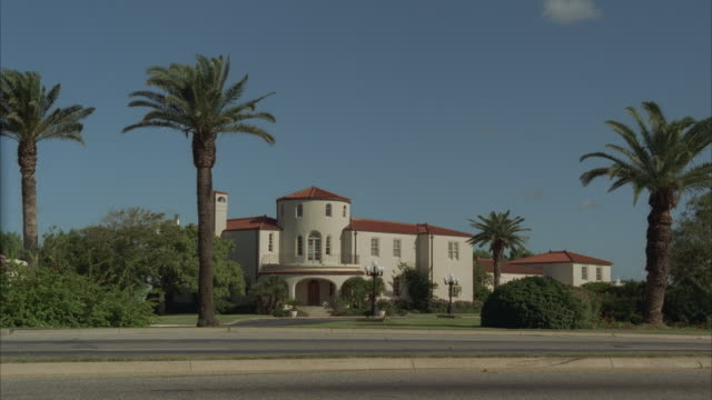MS, Cars passing large two-story mansion, Corpus Christi, Texas, USA