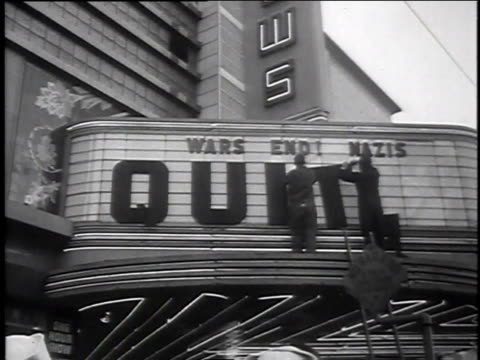 cars passing theater / worker puts up nazis quit on theater marquee / men celebrate and cheer / sailors waving newspapers at camera and cheering - ve day stock-videos und b-roll-filmmaterial