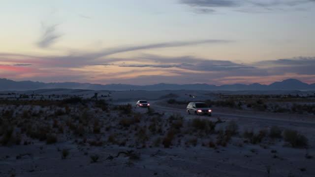 WS PAN Cars passing through desert at night / Santa Fe, New Mexico, United States