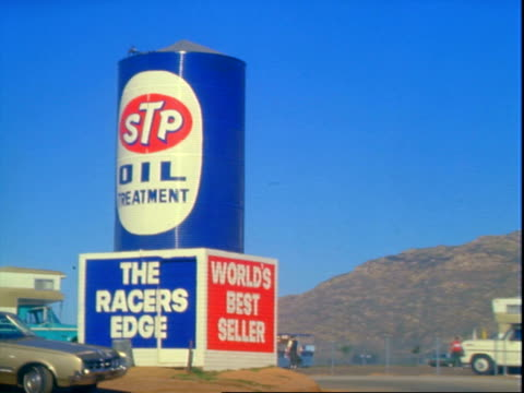 cars passing through main entrance to riverside international raceway / stock car racing giant inflatable stp oil can display near parking lot / blue... - motor oil stock videos and b-roll footage