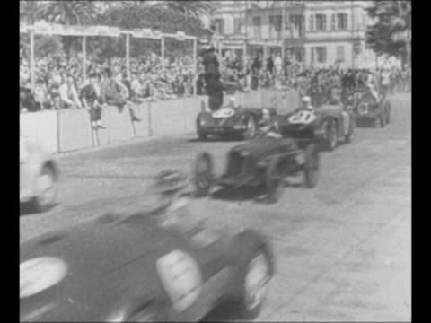 vídeos de stock, filmes e b-roll de cars pick up speed on track at nice grand prix race / cars approach pass / cars round corner as people watch from corner and from building behind /... - paramount building
