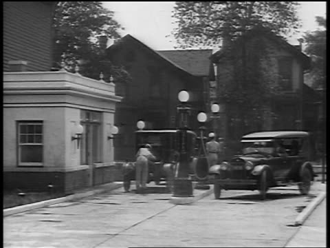 b/w 1929 cars pulling up to gas station / newsreel - 1920 1929 stock-videos und b-roll-filmmaterial