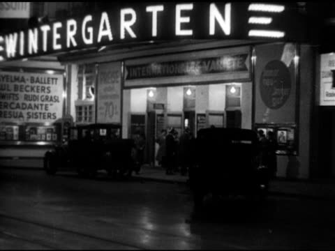 Cars pulling up to sidewalk of Wintergarten Variete Theatre People walking past advertising poster for Fritz Lang's 'Nibelungen Siegfried Die' w/...