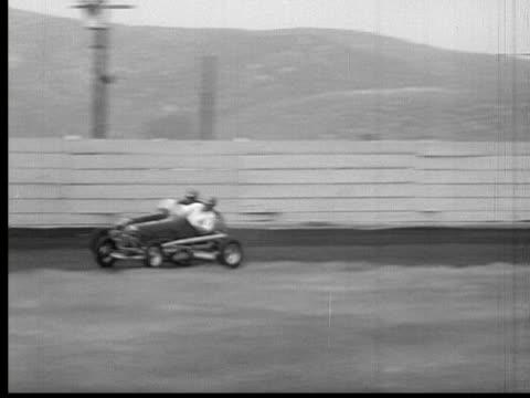 1947 B/W MONTAGE CU MS POV PAN Cars racing around speed track, one car crashing into boundary, USA, AUDIO