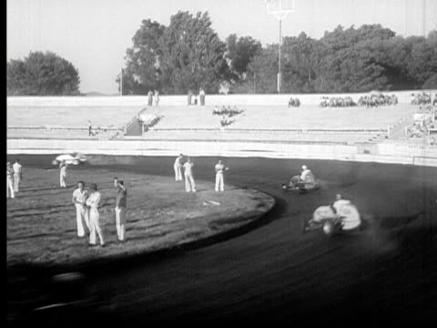1948 B/W MONTAGE MS WS HA POV Cars racing around speed track, three men cheering from side of track, USA, AUDIO