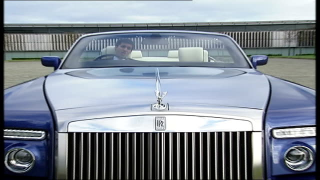 rolls royce new car phantom coupe preview ext close shot phantom emblem on bonnet rising into place pull out to reporter to camera to - rolls royce stock videos & royalty-free footage