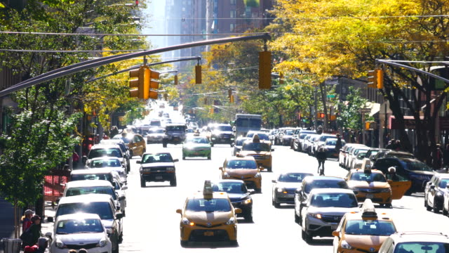 Cars run on Madison Avenue and people cross, which is illuminated by autumn sunlight at Upper East Manhattan New York.
